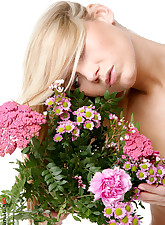 Lovely blond and tall beauty playing with flowers